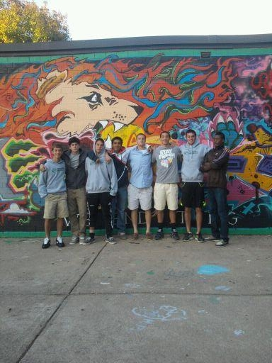 The nine seniors gather in front of the senior wall. The boys have become a family throughout their years on the team. Photo courtesy of Anne Cushman.