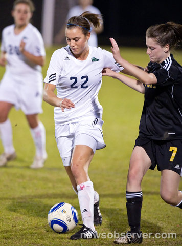 Caroline Gentry stiff-arms an Apex defender last year. Based on her performance during the 2011 season, Gentry was named the North Carolina women's soccer player of the year and eventually to the All-American team.