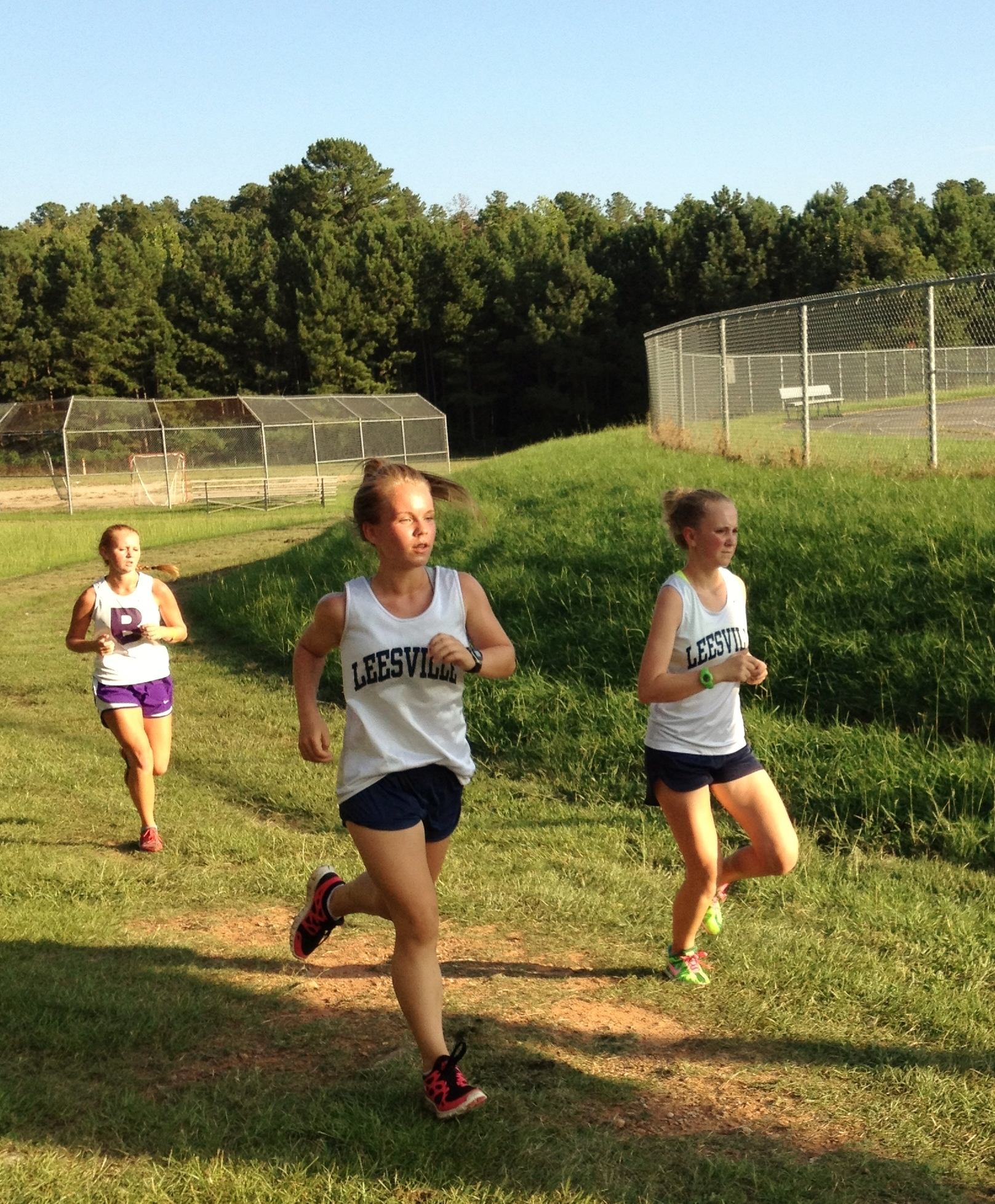 Abby Tarnowski (center), sophomore, and Jessica Merdes (right), senior, race to the finish in a Leesville cross country meet against Broughton. Tarnowski and Merdes were both happy with their races.