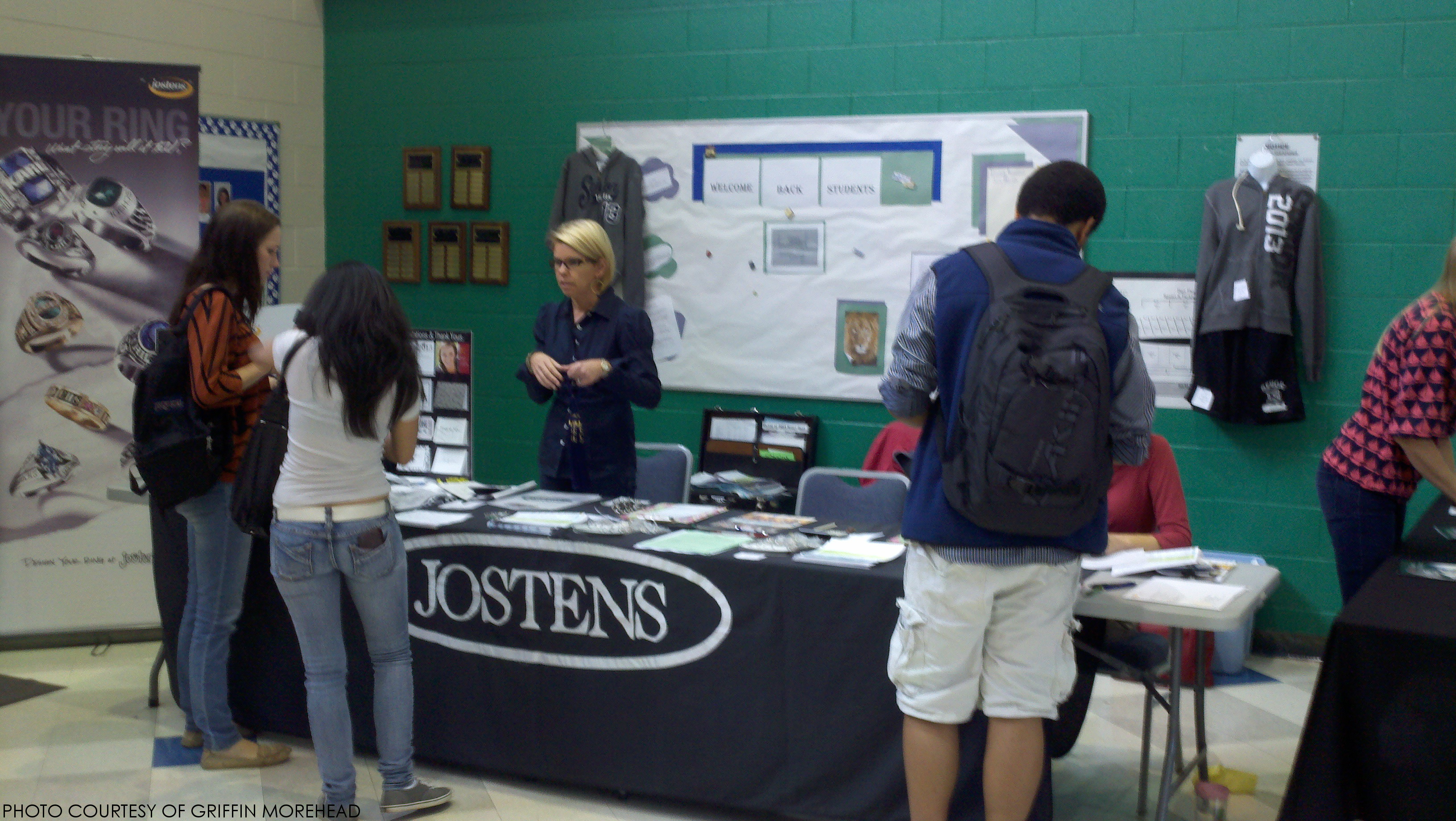 A Jostens representative helps several students at the Jostens stand on October 2.  Jostens was selling graduations caps, gowns and announcements, as well as class rings.