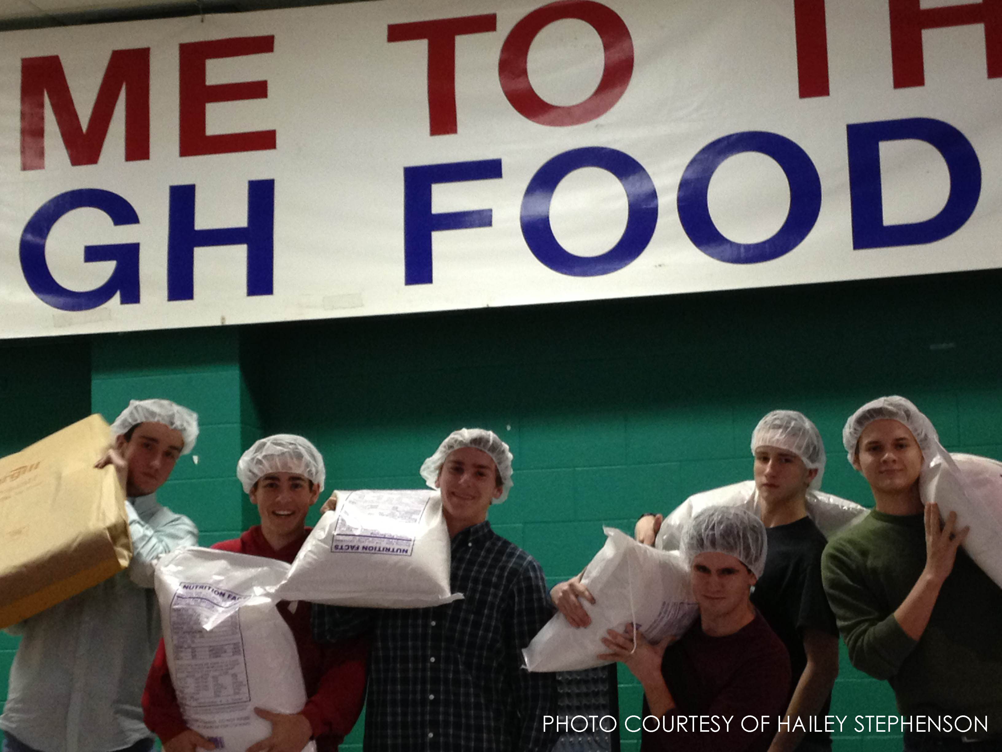 Several guys pose holding large bags filled with the ingredients needed to package meals. 20,000 meals for needy families worldwide were assembled that day.