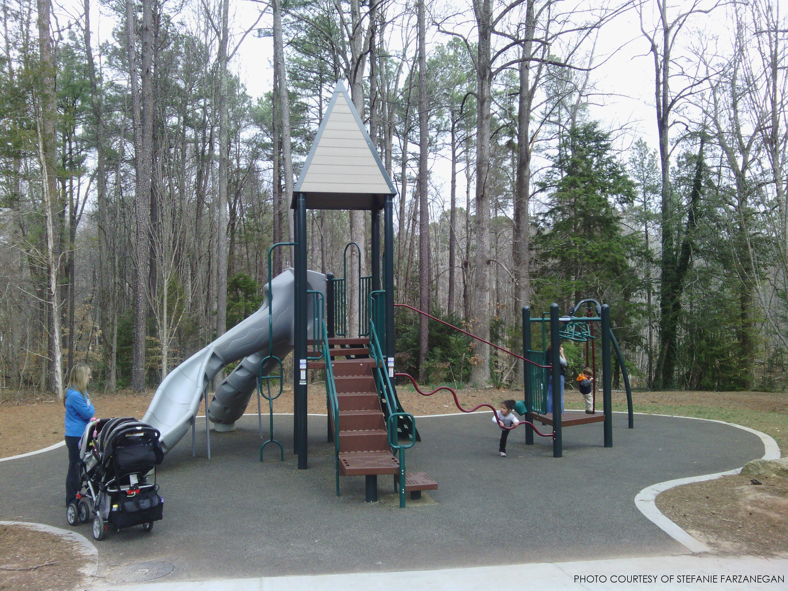 A picture of the Strickland Road Park in Raleigh, NC.  What makes this park great is the variety of climbing equipment for kids to explore, while the lack of moving parts make this playground less risky.