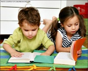 A posed photo of two preschool-age kids reading much bigger books than they should. Today's young kids are not always given the room that they should be given to learn creatively.