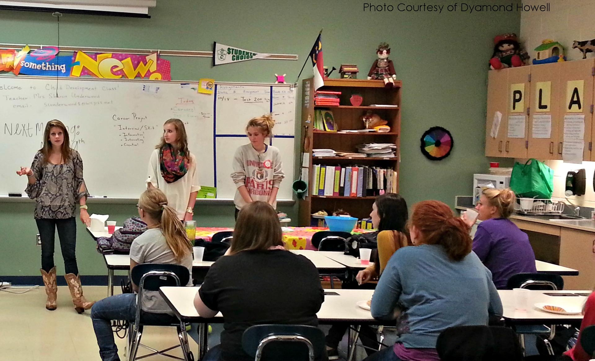 ECE members listen intently as Hannah Mathis, president, Shannon Kearney, vice president, and Sterling Shelly, treasurer, talk about future plans for the club. Community service hours that are received in ECE can be used as service hours for NHS.
