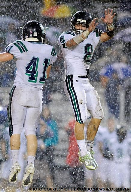 Braxton Berrios (#8) and Max Reconnu (#41) celebrate a big play as the rain pours down at Millbrook. Berrios scored Leesville's only touchdown in a 7-3 win.