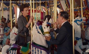 A photo captured from a scene in Saving Mr. Banks in which Walt Disney (Tom Hanks) coerces P.L. Travers, (Emma Thompson) the reclusive author of Mary Poppins, to ride on a  Merry go round at Disney World. Saving Mr. Banks illustrated the real-life story of Walt Disney's pursuit to make Marry Poppins a movie.