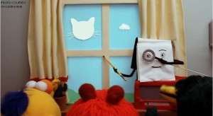"""The notebook from """"Don't Hug Me I'm Scared"""" holds a magnifying glass to its eye in order to show the puppets the """"correct"""" way to look at the clouds. This particular scene illustrates the media manipulation in children's shows which promote a certain point of view."""
