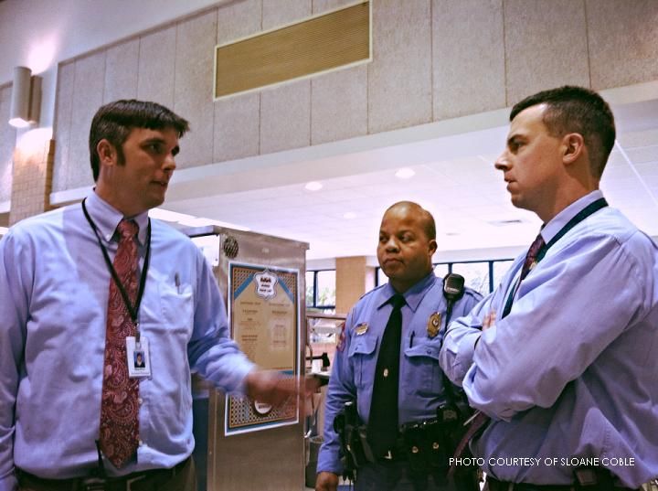 Mr. Price, far left, converses with Deputy Greene and Dr. Muttillo.