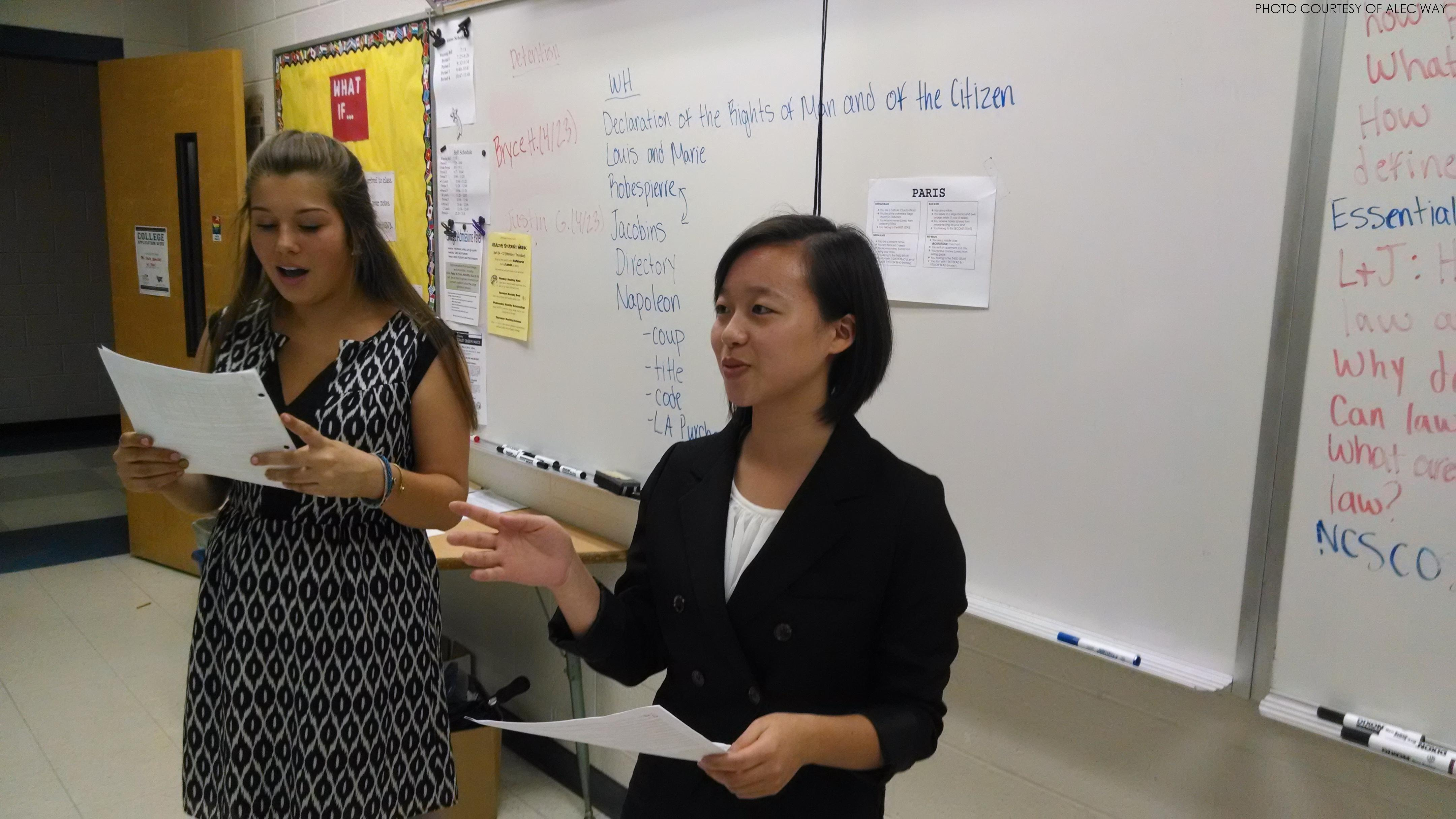 Deborah Yoo (senior) and Eugenie Riga (junior), defense attorneys in a case involving a car accident, stand for their closing statement. The trial consists of an opening statement, followed by the direct and cross examination of witnesses for both sides, ending with each sides' closing arguments.