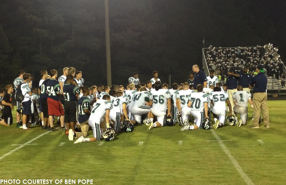 Mike Hobgood, head coach, and assistants address the team solemnly after Thursday's 44-14 loss to Apex.