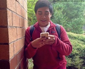 Othman Fatfat enjoys his new phone after school at carpool.  His phone runs faster thanks to the speed of data reception on the iPhone 6.