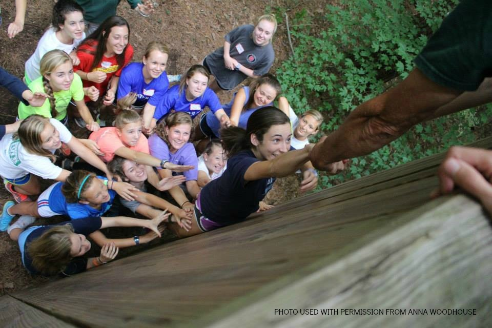 Nevada Mareno (center) is raised over a 12-foot wall by her teammates during a section of the low ropes course. The team traveled to Town of Cary's ropes course in August to bond as a team