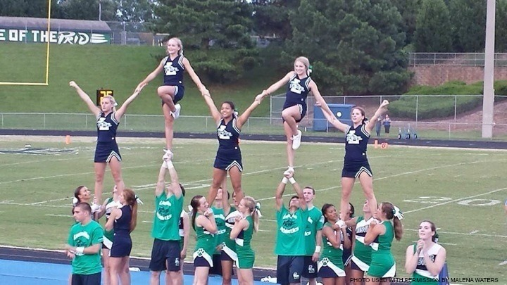 The Leesville varsity co-ed team performs a pyramid as they cheer on the football players in the first game of the season