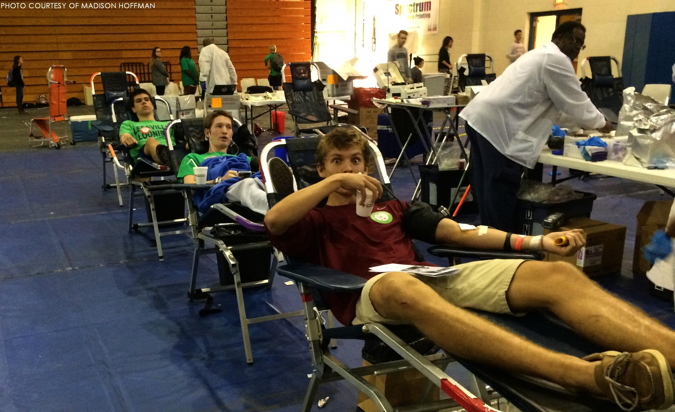 Joe Talbert, Ethan Cornelius and Clay Boneham sitting in their cots as they begin the process of giving blood to the American Red Cross.