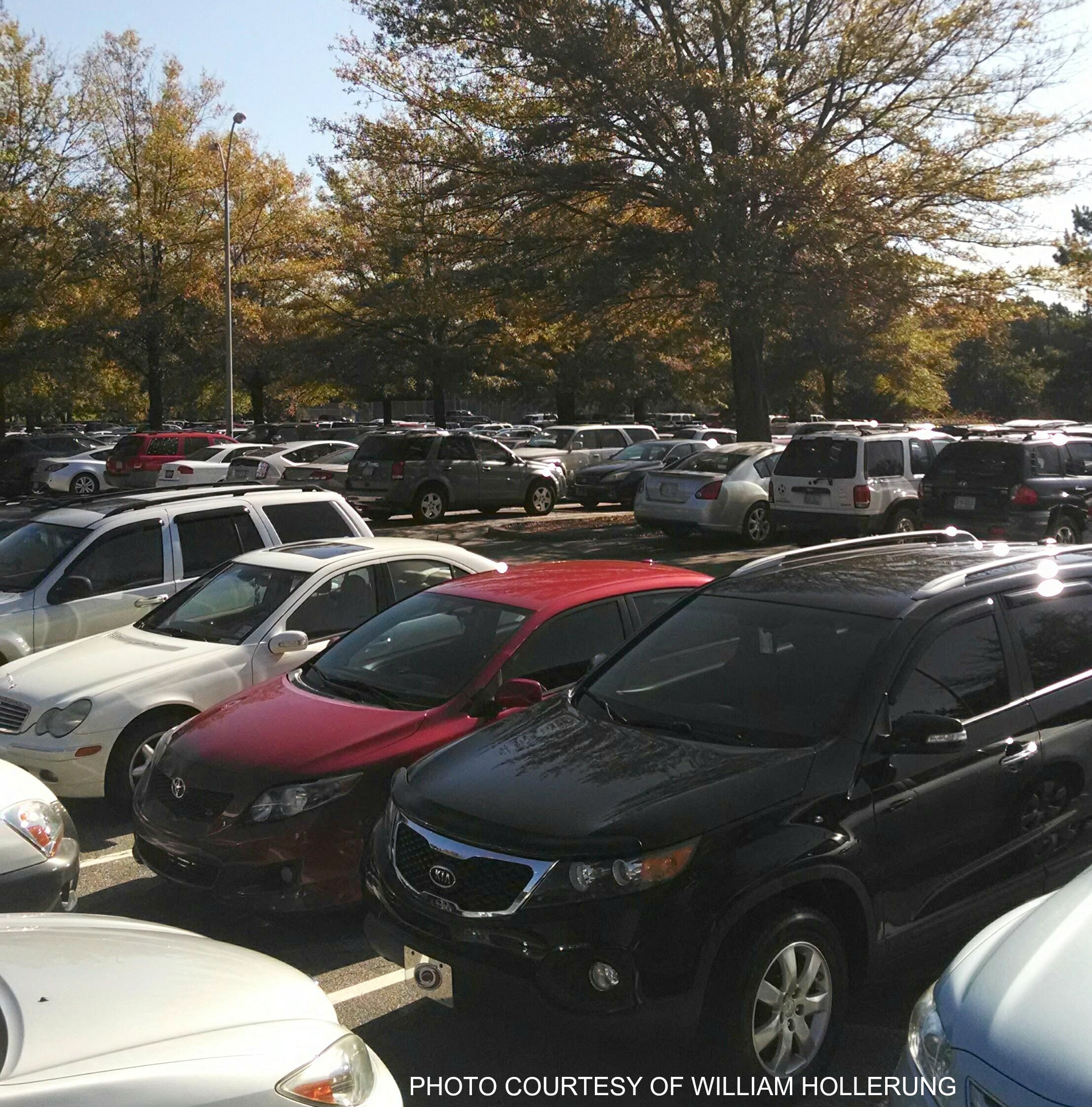 An early afternoon photo of the student parking lot. Every morning, the parking is bustling with students and cars parking and arriving to school in order to learn.