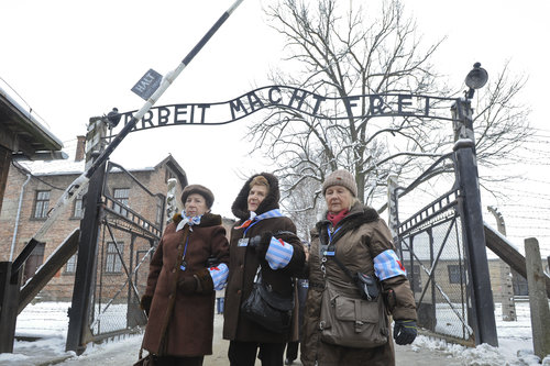 Holocaust survivors walk outside the gates of the Auschwitz-Birkenau camp on Tuesday. Auschwitz was the largest of the Nazi concentration camps.