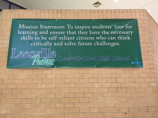 """""""To inspire students' love for learning and ensure that they have the necessary skills to be self-reliant citizens who can think critically and solve future challenges."""" This banner, bearing the Leesville mission statement, hangs in the front lobby."""