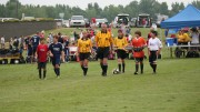 USSF-certified referees and the captains of each team prepare to start the game with the coin toss. Certification courses teach aspired referees the rules and regulations of soccer games.