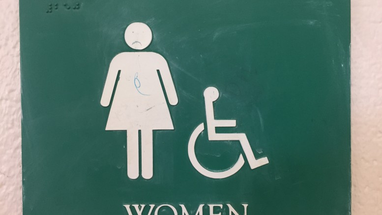 "The ""Women"" sign outside of a bathroom at Leesville. Someone has drawn a frowny face on the picture, reflecting the public opinion about the quality of the bathrooms. (Photo Courtesy of Maggie Pollard)"