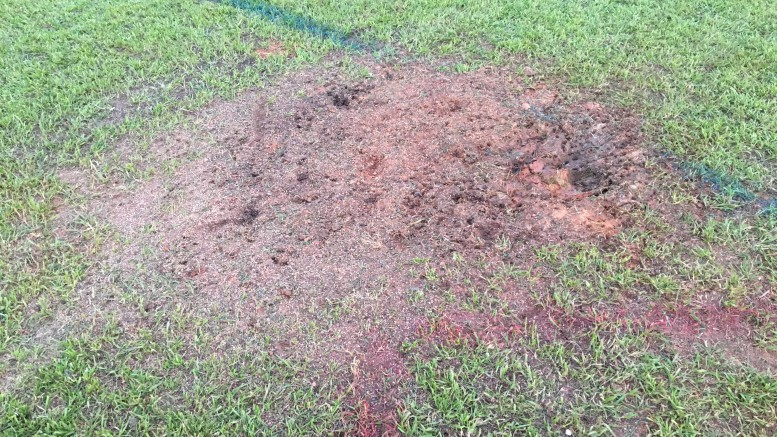 The broken pipe has caused a hazardous area on the field. It is located near the left hand corner of the field and is made up of soggy sand, rocks and soil.