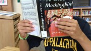 A student in the library reads To Kill a Mockingbird. The novel has been a classic for years and is still widely enjoyed by students.