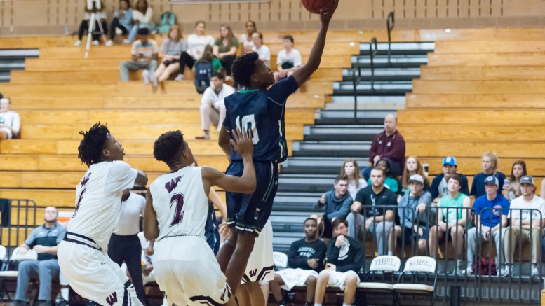 DJ Horne, sophomore guard, makes a move past the defender for a layup. The Pride secured a necessary conference win Friday night at Wakefield. (Photo used by permission of Bob Stewart)
