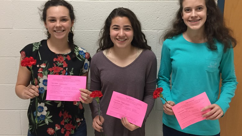 Three students pose with their carnations and singing valentines. Singing Valentines are an opportunity for students to spread love and appreciation to their friends or significant others. (Photo Courtesy of Jonathan Spear)