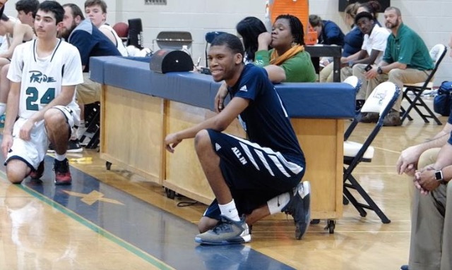Jayvin Talley, a Millbrook men's junior varsity basketball manager, waits to enter the game against Leesville. Talley, a student with special needs, scored a layup in the final seconds of the game, his first appearance in a game this season for the Wildcats. (Photo used by permission of Evan Moesta)