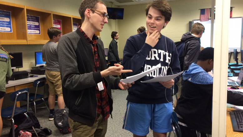 Carlyle Ivey, student teacher, helps Jackson Webb, sophomore, with his performance task in English class in order to improve his skills. Ivey is a student teacher for Monica Wilkerson and is assisting her with her English II Honors and Academic classes this semester. (Photo courtesy of Erin Darnell)