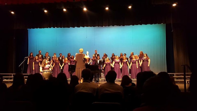 The Capital Pride choir hold hands while performing a song, during the Spring Concert. Capital Pride is led by Tonya Dickens, and student conductors Collin Dail and Nola Baldwin. (Photo Used by Permission of Loren Wait)