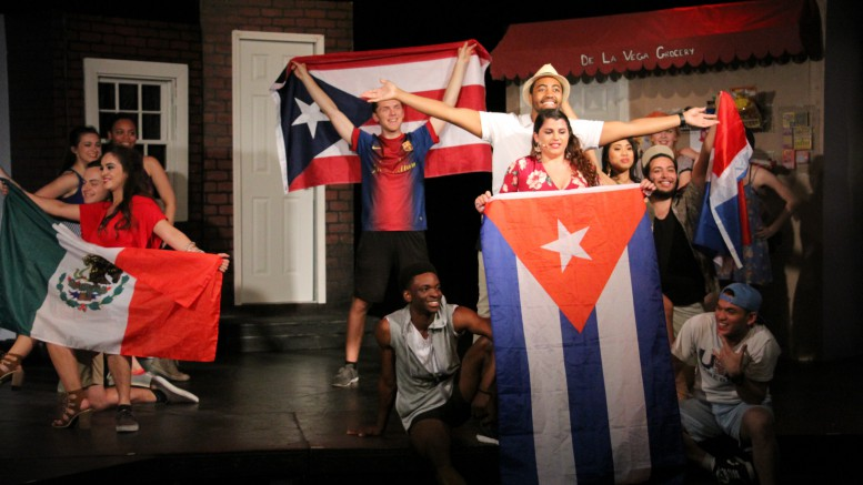 Cast members hold up flags from various Spanish-speaking countries. In the musical, the majority of the neighbors in Washington Heights are from Puerto Rico and the Dominican Republic. (Photo used by permission of Drake Broussard.)