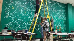 Carson Rainey dips her paintbrush as fellow seniors get to work. A painting of a multicolored lion, the artwork is a near replica of that of the one painted by the parking circle outside. (Photo Courtesy of Ray Youman)