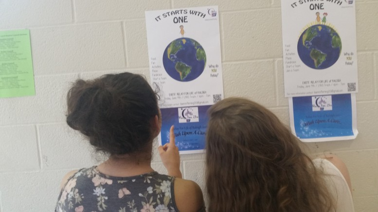 A few Leesville students view the display of Relay for Life posters in the main lobby. They consider participating in the relay this June. (Photo Courtesy Hannah Comesky)