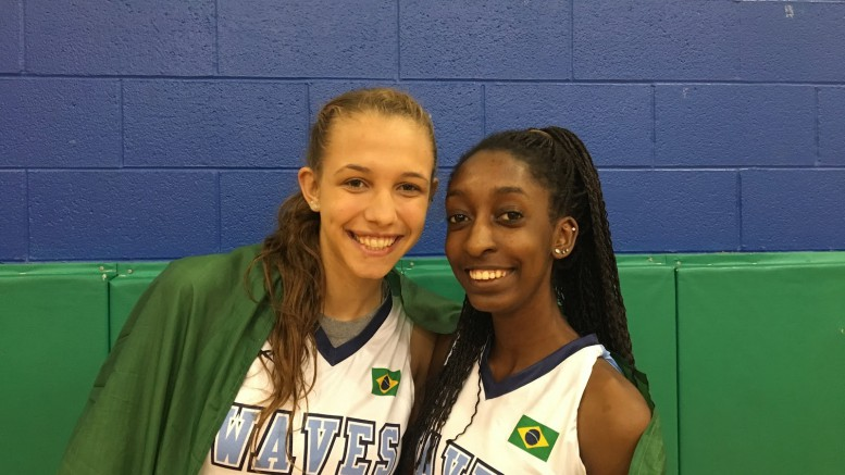 During their travel team basketball practice at LRMS, Izabel Varejão (left) and Geassy Germano (right) pose proudly with the Brazil flag on their jerseys and draped around their back. Both girls have lived with local Leesville families during the two years they've been in the US. (photo courtesy of Lucy Leen)