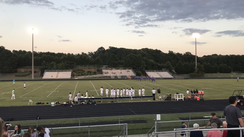 The varsity soccer team stands in front of their bench, waiting for the game to begin. Follow @LRHSnews on Twitter for updates on sports events such as this one. (Photo courtesy of Natalie Gore.)