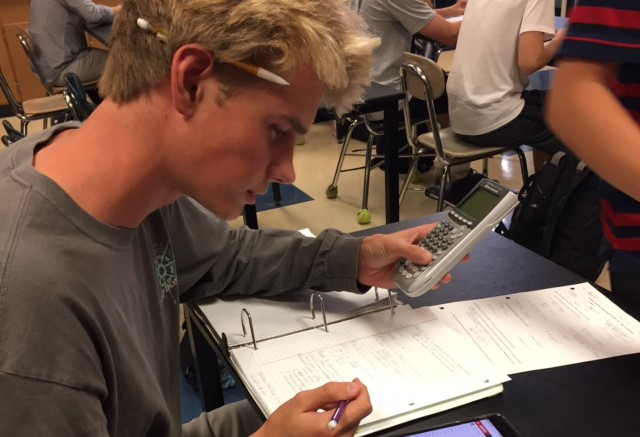 Henry Lee, Sports Statistics Club president, calculates his projected fantasy football score. The club meets in Mrs. Cade's room every third wednesday of the month. (Photo Courtesy of Ben Zahavi)