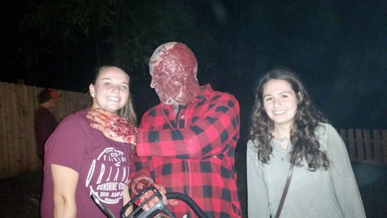 Addison Bordeaux (left) and Camryn Brockman (right) pose with a person dressed up and working at panic point. They decided to go to panic point on opening night-- nearly 4 weeks before Halloween-- to take advantage of the shorter lines.