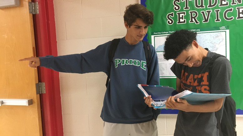 Gustavo De Oliveira, a junior at Leesville Road High School (left), gives directions to a freshman. Freshman, in most circumstances, are clueless on the first day of school. But with assistance from their peers, their high school career can be a lot more comfortable. (Photo courtesy of Sarah Jumma)