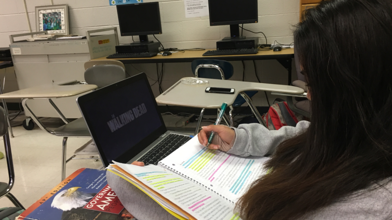 Francine Simbulan, a sophomore at Leesville Road High School, shows how tempting technology can be. Once someone's train of thought has been interrupted and they are distracted from the task at hand, it takes an average of 25 minutes to return to that task. (Photo courtesy of Sarah Jumma)