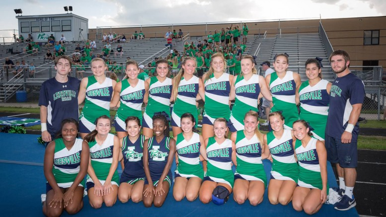 The Pride cheerleading team pose for a photo before a home football game against the Wakefield Wolverines. Matthew Carroll,sophomore, far left, and Adam Gee, far right, far right, are currently the only two male cheerleaders on the team. (Photo used by permission of Lori Campoli)